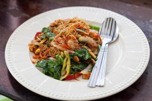 Drunken noodles fried with pork in a white dish