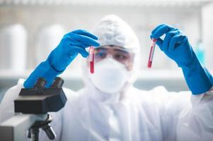 Researcher holding two blood samples