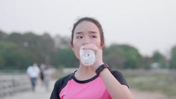 Young Asian Woman Drinking Water After a Run