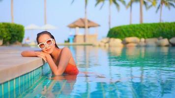 mulher asiática sorrindo enquanto toma banho de sol na piscina com palmeira em frente ao mar