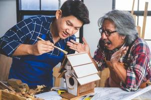 Two men painting a birdhouse