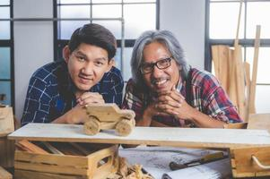 Two carpenters with a wooden car