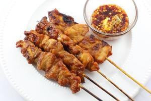 Grilled chicken skewers with sticky rice and chewy sauce on a white background