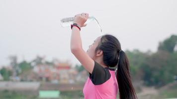 Young Asian Woman Pouring Water on Her Head to Refresh After a Workout