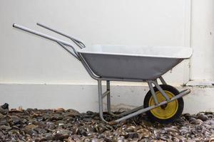 Yellow wheelbarrow on wet river stones