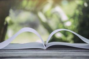 Cuaderno y lápiz blanco sobre una superficie de madera con un fondo de naturaleza borrosa foto