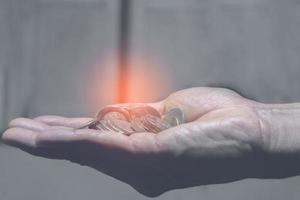 monedas en la mano, finanzas y concepto de ahorro de dinero foto