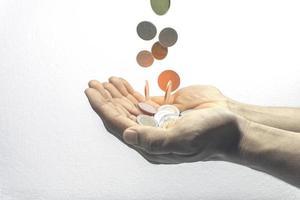 monedas cayendo en manos, finanzas y concepto de ahorro de dinero foto