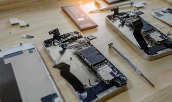 Smartphone motherboard repair by a professional technician on a desk photo