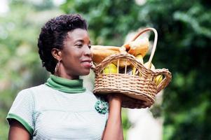 Young woman holding a basket of fruit in her hand and going for a picnic