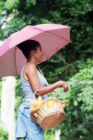 Young woman with an umbrella holding a basket filled with food