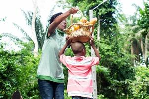 mamá poniendo la canasta de comida en la cabeza de su hijo como él quiere foto