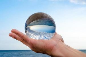 Man holding a glass orb lens photo