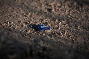 Bud Light bottle cap littered on a dirt ground in the USA