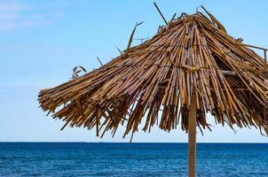 Straw umbrella on a beach photo