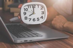 A hand holding a clock on a work desk photo