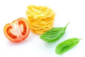 Italian food concept of fettuccine with tomato and sweet basil isolated on a white background photo