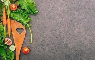 Wooden spatula and vegetables on a dark stone background. Healthy food and cooking concept.
