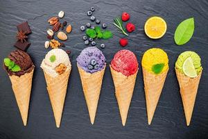 Various ice cream flavors in cones on a dark stone background. Summer and sweet menu concept.