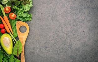 Healthy food and cooking concept with a wooden spatula and vegetables on dark stone background. photo
