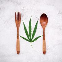 Imagen conceptual de alimentos de una hoja de cáñamo con una cuchara y un tenedor sobre fondo de hormigón blanco foto
