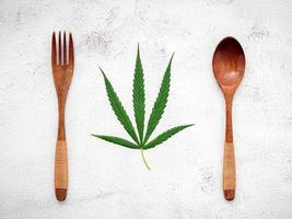 Food conceptual image of a hemp leaf with a spoon and fork on white concrete background