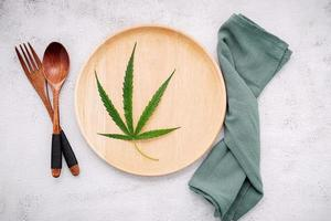 Imagen conceptual de alimentos de una hoja de cáñamo con una cuchara y un tenedor sobre fondo de hormigón blanco