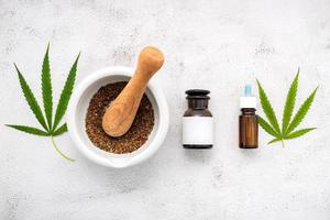 Glass bottle of hemp oil with a white mortar and hemp leaves set up on a concrete background, aromatherapy concept photo