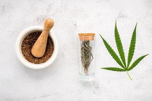 Glass bottle of hemp oil with a white mortar and hemp leaves set up on a concrete background, aromatherapy concept