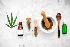 Botella de vidrio de aceite de cáñamo con un mortero blanco y hojas de cáñamo sobre un fondo de hormigón, concepto de aromaterapia