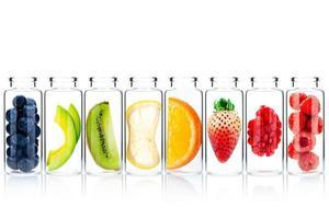 Cuidado de la piel casero con ingredientes de frutas de aguacate, naranja, arándano, granada, fresa y frambuesa en botellas de vidrio aisladas sobre fondo blanco. foto