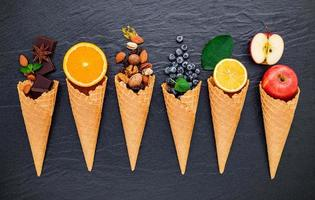 Various ingredients for ice cream flavors in cones showing blueberries, lime, pistachio, almonds, orange, chocolate, vanilla, and coffee set up on a dark stone background. Summer and sweet menu concept.