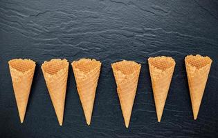 Flat lay of ice cream cones on a dark stone background, crispy ice cream cone with copy space for sweets menu design