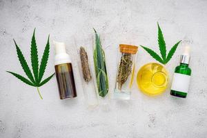 Glass bottles of hemp oil and hemp leaves set up on a concrete background