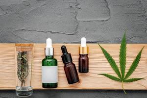 Botellas de vidrio de aceite de cáñamo y hojas de cáñamo sobre un fondo de hormigón