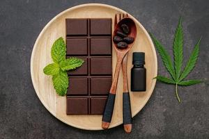 Cannabis leaf with dark chocolate, plant leaves, and wooden utensils on a dark concrete background