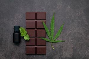Hoja de cannabis con chocolate negro, hojas de plantas y utensilios de madera sobre un fondo de hormigón oscuro foto