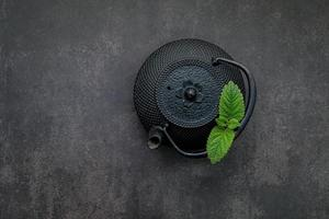 Black cast iron tea pot with herbal tea set up on a dark stone background