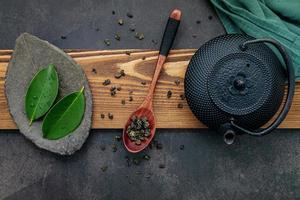 Black cast iron tea pot with herbal tea set up on a dark stone background photo