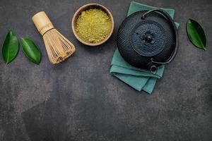 Tetera de hierro fundido negro con té de hierbas sobre un fondo de piedra oscura foto