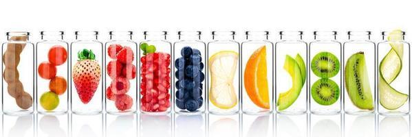 Cuidado de la piel casero con ingredientes de frutas de aguacate, naranja, arándano, granada, kiwi, limón, fresa y frambuesa en botellas de vidrio aisladas sobre fondo blanco. foto