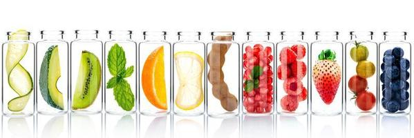 Cuidado de la piel casero con ingredientes de frutas de aguacate, naranja, arándano, granada, kiwi, limón, pepino, tamarindo, fresa y frambuesa en botellas de vidrio aisladas sobre fondo blanco. foto