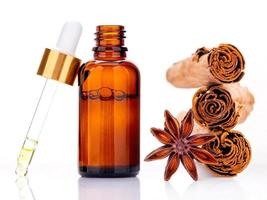 Cinnamon essential oil bottle with Ceylon cinnamon sticks and anise star isolated on a white background photo