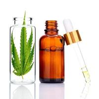 Green hemp leaves with oil bottle and dropper isolated on a white background photo