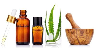Glass bottles of oil and hemp leaf isolated on white background