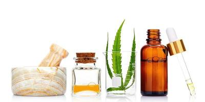 Glass bottles of oil, pestle and mortar, and hemp leaf isolated on white background