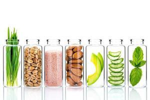 Cuidado de la piel casero con ingredientes naturales y hierbas en botellas de vidrio aislado sobre un fondo blanco. foto