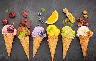Various ice cream flavors in cones of blueberry, green tea, pistachio, almond, orange, and cherry on a dark stone background. Summer and sweet menu concept