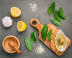 Ingredients for homemade pesto sauce of basil, parmesan cheese, garlic, olive oil, lemon, and Himalayan salt over a dark concrete background photo