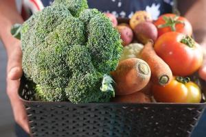 manos sosteniendo una caja de verduras foto
